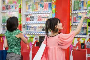 Young women choosing drinks from a vending machine